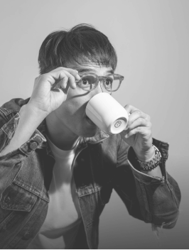 Sky holding his eyeglasses drinking from a cup