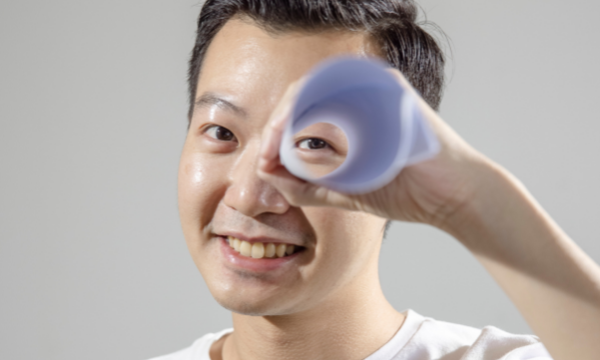 A man holds a rolled up piece of paper to his eye