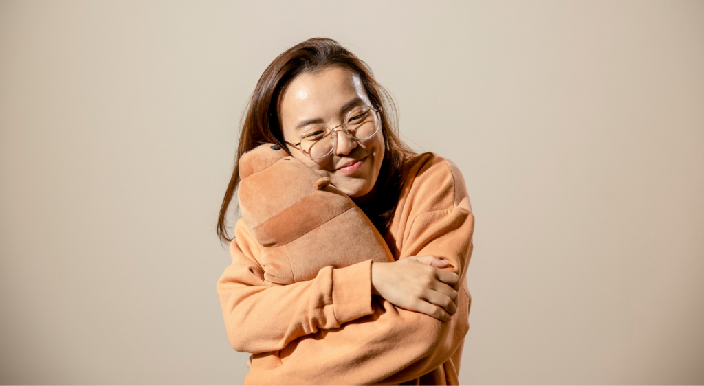 A girl holding a bear soft toy