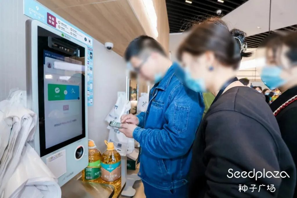 People at a self-service check-out machine